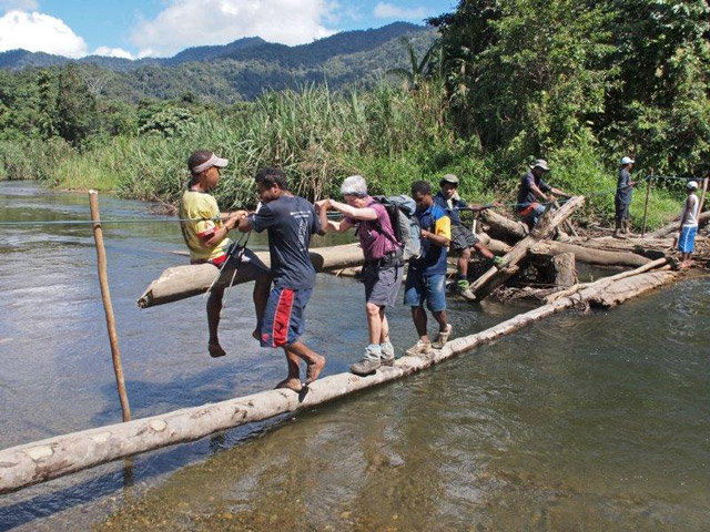 Crossing the Brown River on a makeshift bridge
