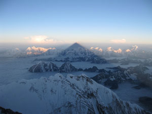 Looking west, the shadow of Everest stretches over Nepal as the sun rises behind on a spectacular summit day